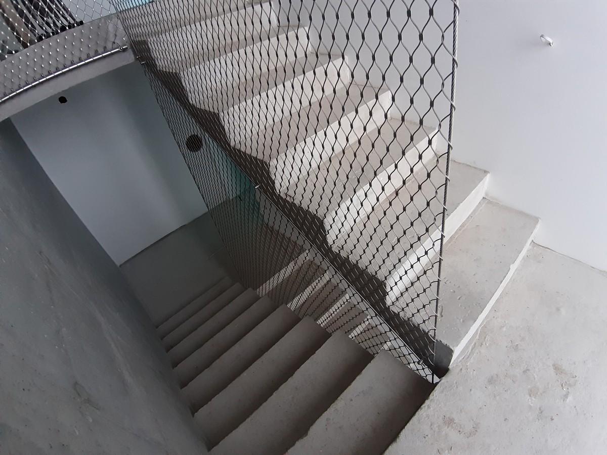 Zabezpieczenie z siatki w duszy schodów